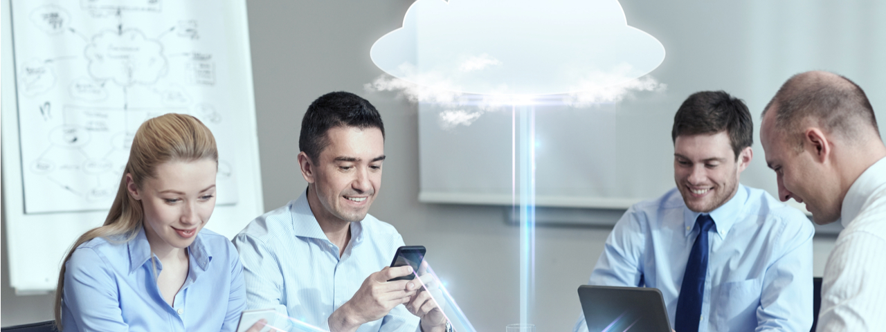 Four business people using computers or phones connected by cloud